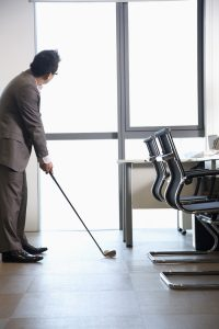A business man practices his golf swing indoors during the winter months