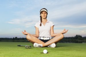A female golfer practicing yoga while on the golf course